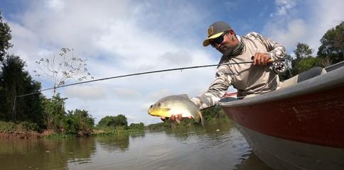 Homem segurando um peixe pacu na beira do rio